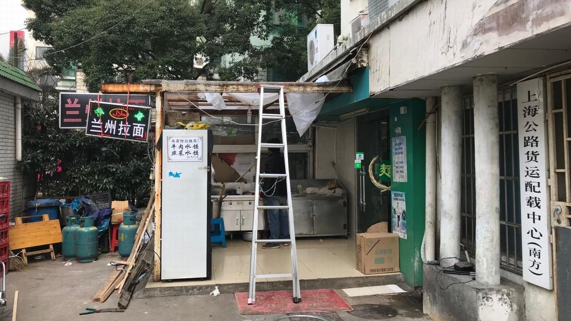 電気の配線か何かを修理中の、蘭州牛肉麺のお店の入り口